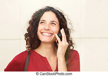 Close up happy young woman smiling and talking on cellphone