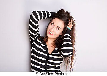 Close up happy young woman smiling with hands in hair