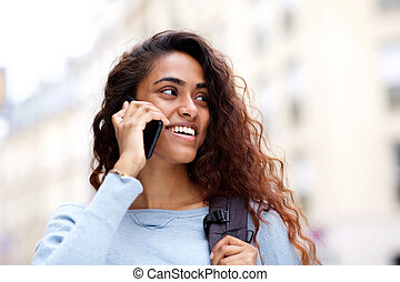Close up happy young woman talking with cellphone outside in city