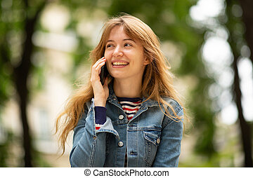Close up happy young woman talking with mobile phone in park