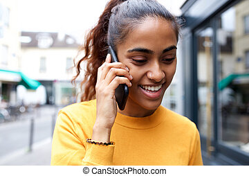 Close up happy young woman talking with smart phone in city