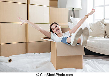happy young woman unpacking boxes in new apartment