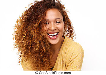 Close up happy young woman with curly hair laughing against white background
