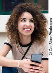 Close up happy young woman with curly hair sitting outside with cellphone