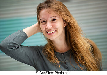 Close up happy young woman with hand in hair