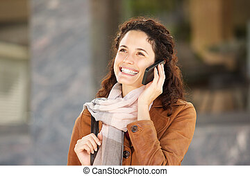 Close up happy young woman with scarf talking on mobile phone