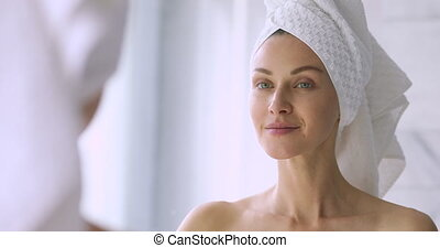 Close up head shot attractive young woman with bowel on head, applying moisturizing balm creme after morning shower in bathroom. Happy beautiful lady hydrating skin, enjoying daily skincare routine.