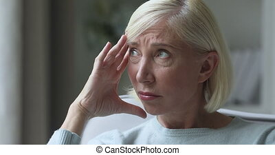 Close up head shot unhealthy frowning mature older woman touching temples, suffering from strong head ache alone at home. Unhappy stressed middle aged granny having high blood pressure migraine.
