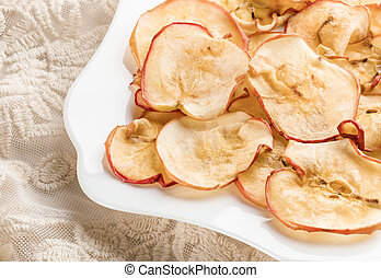 Close-up healthy apple chips on white figured plate on lace fabric.