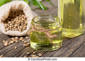 Close-up hemp oil in glass jar and bottle with cannabis grains in sack on wooden board.