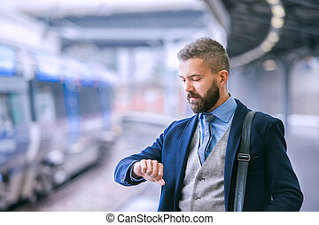 Close up, hipster businessman waiting at the train station