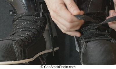 hockey player tightening laces on his skates