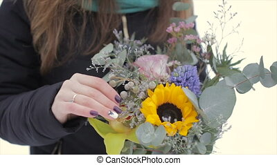 Close-up, holding a bouquet of flowers on a winter day
