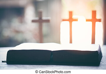 Close up holy bible with Three cross on wooden table. Christian concept