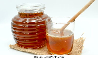 Close up honey dropping with wooden. Dipper in a glass place on the sack.