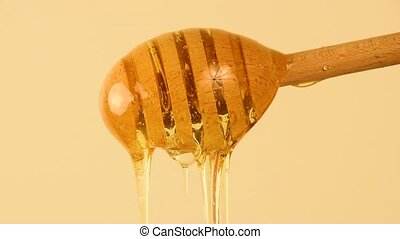 Close up honey flowing from wooden dipper on beige - Close...