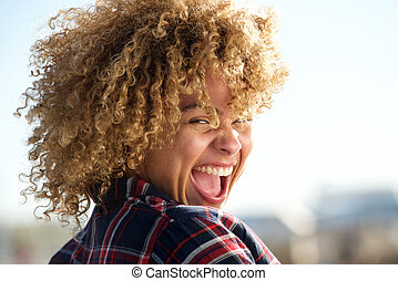 beautiful african american woman laughing outdoors