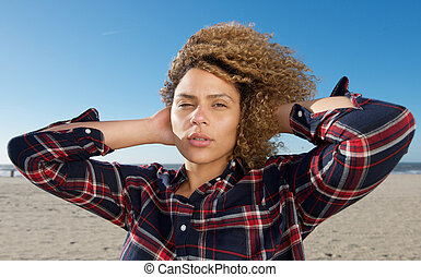 horizontal portrait beautiful african american woman with hand in hair at beach