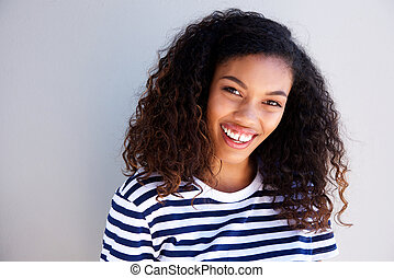horizontal portrait of beautiful young african woman smiling against white wall