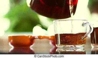 Hot Aromatic Fresh Tea Is Poured Into A Glass Mug - Close-up...