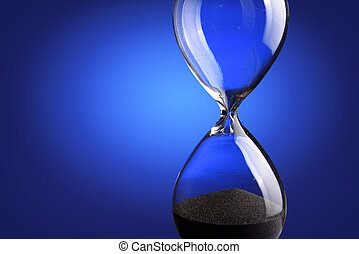 Close up hourglass on blue background