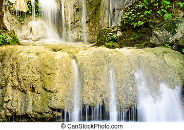 Large round limestone rock with soft silk stream gushing through at Thac Voi waterfall of tropical rainforest in Thanh Hoa province, Vietnam
