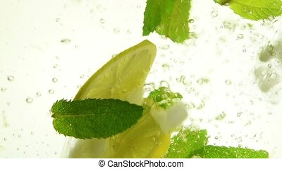 Close up ice cubes, mint leaves, lemon in mojito