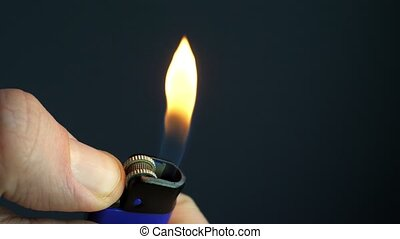 Close up ignite of cigarette lighter in the hand with flame.