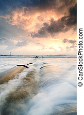 close up image. beautiful sea view with soft waves hitting concrete drainage pipe on the beach over sunrise background and dramatic dark clouds. infinity focus and long exposure shot