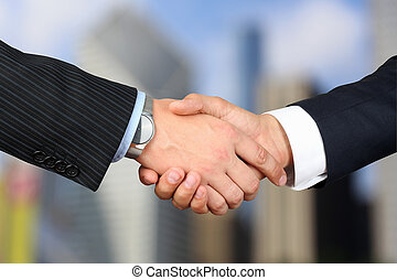 Close-up image of a firm handshake between two colleagues outsi