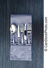 Close-up image of a folded napkin with utensils on the wooden table. Cutlery in a napkin close-up of a wooden background