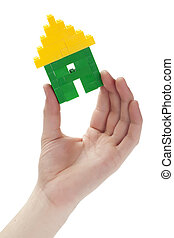 a hand holding a house lego