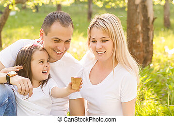 Close-up image of a young happy family spending their weekend in the park where the daughter feeding her father with the ice-cream