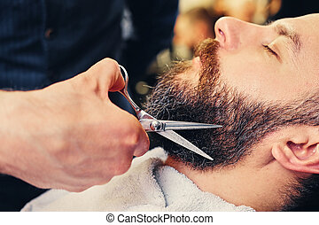 Close-up image of barber makes beard cut of a man.