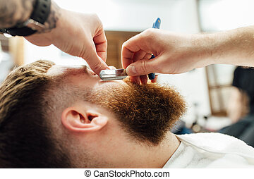 Close up image of barber makes beard cut of a man