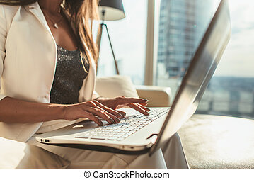 Close-up image of female hands typing on laptop keyboard in modern office