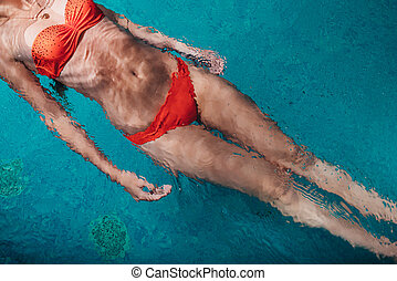 Close-up image of female wearing bikini swimming on back in blue water