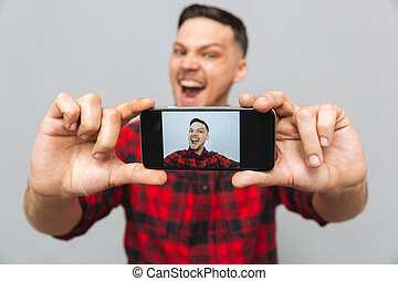 Close up image of happy man making photo on smartphone