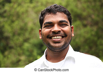 Close-up image of happy, smiling & smart south-asian/indian entrepreneur with satisfied expression. The person is wearing a white shirt & the picture is shot in natural settings