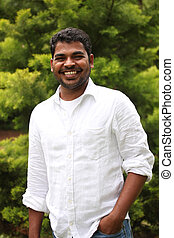 Close-up image of healthy, relaxed & happy asian/indian executive with positive expression. The person is wearing a white shirt & the picture is shot in natural settings