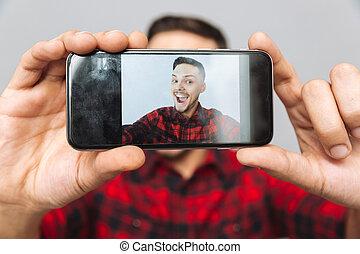 Close up image of man making photo on smartphone