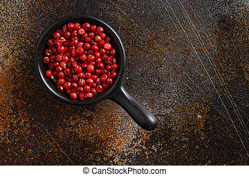 Close-up image of pepper rose, pink peppercorns on black wood background, view above space for text on side