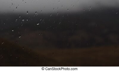 Close up image of rain drops falling on a window at eveing,