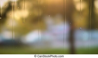 Close up image of rain drops falling on a window . Blurry background