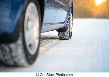 Close-up Image of Winter Car Tire on the Snowy Road. Drive...