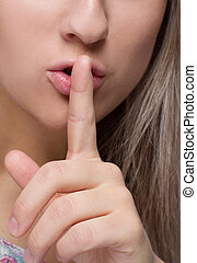 Close-up image of woman with finger on her lips