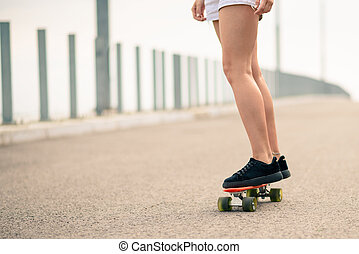 Close up Image of Young Girl`s Legs Riding Orange Skateboard