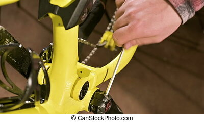 Close-up in a bicycle repair shop, the master installs the...