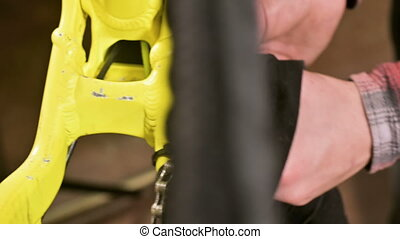 Close-up in a bicycle repair shop the master removes the...