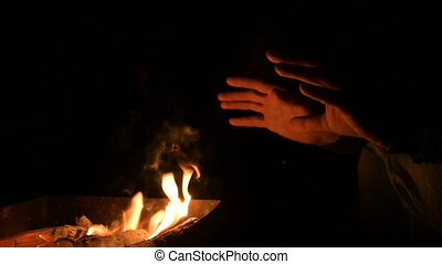 Close-up in complete darkness a man warms his hands on an open fire. Men's palms by the fire at night